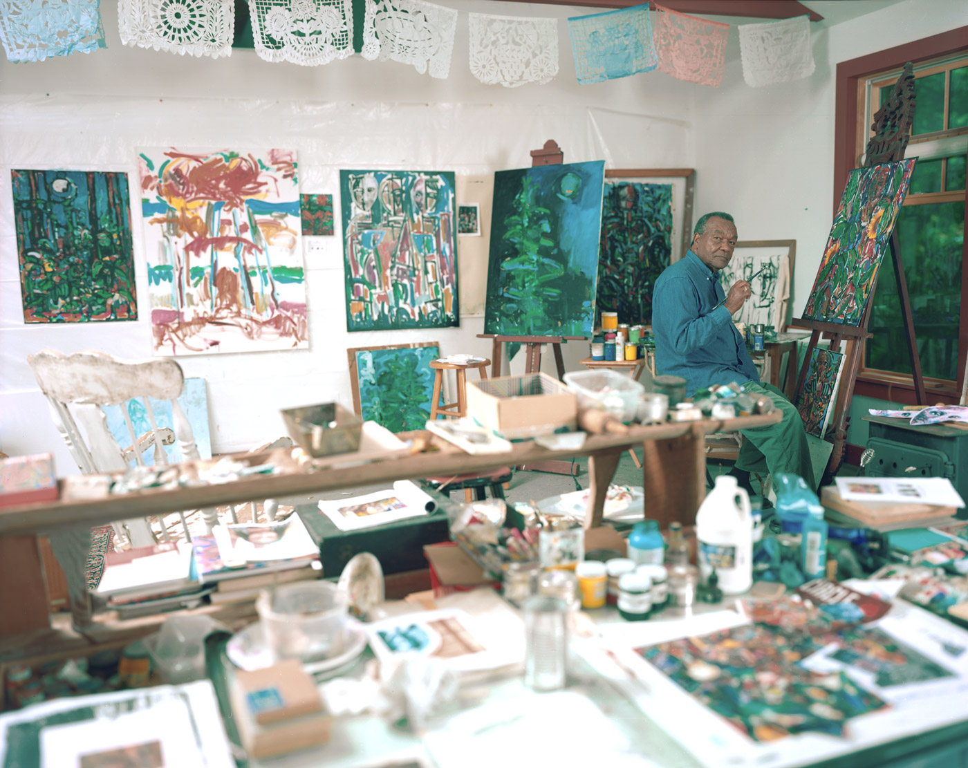Photograph of David Driskell seated at his easel with a paint brush in hand in his studio surrounded by paintings.