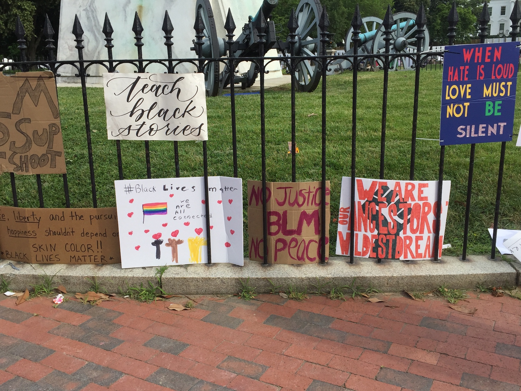 Hand-drawn protest signs hang on black bars of a fence in front of a green lawn.