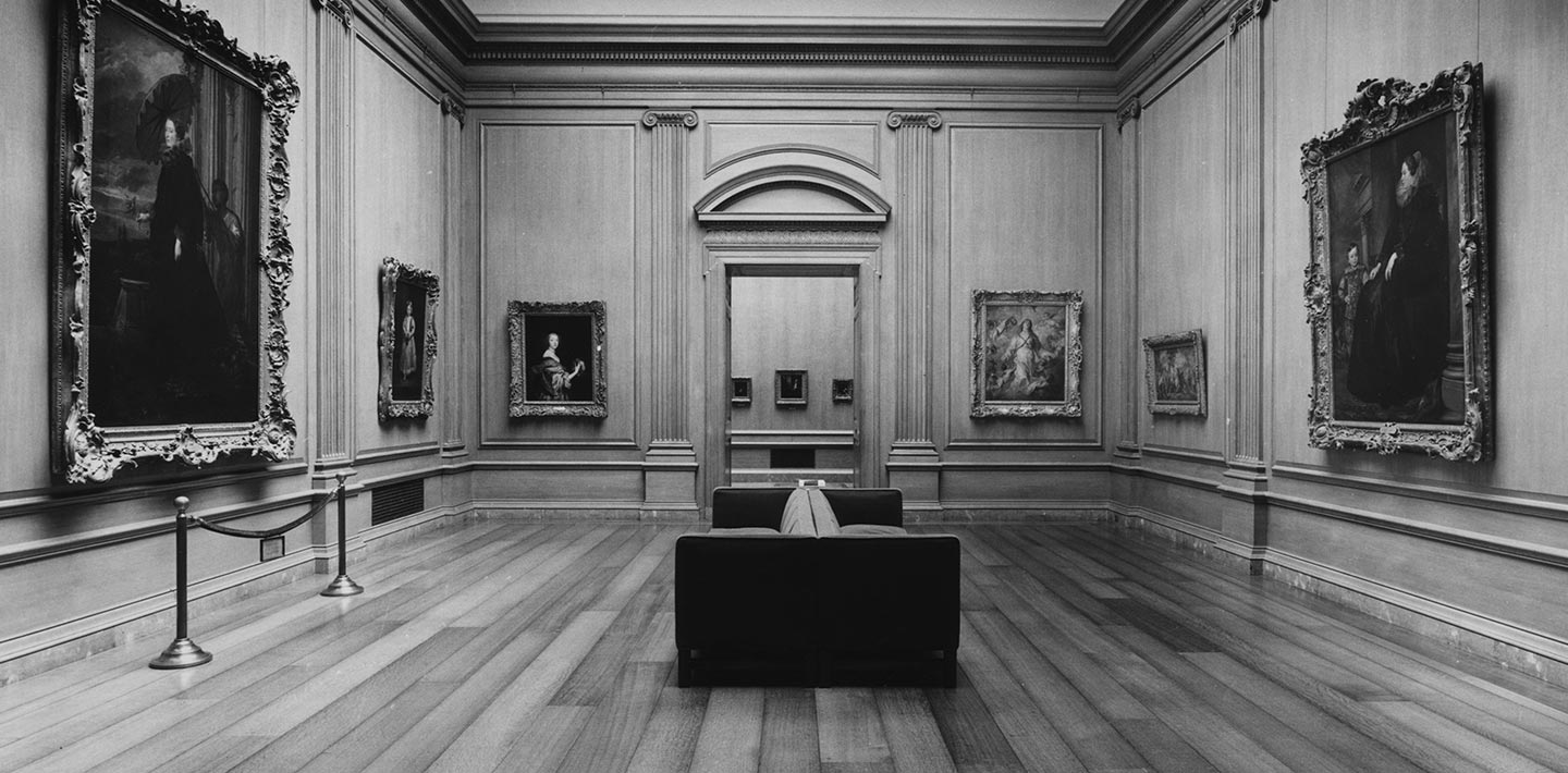 A large gallery stands empty with a large doorway in the center surrounded by paintings