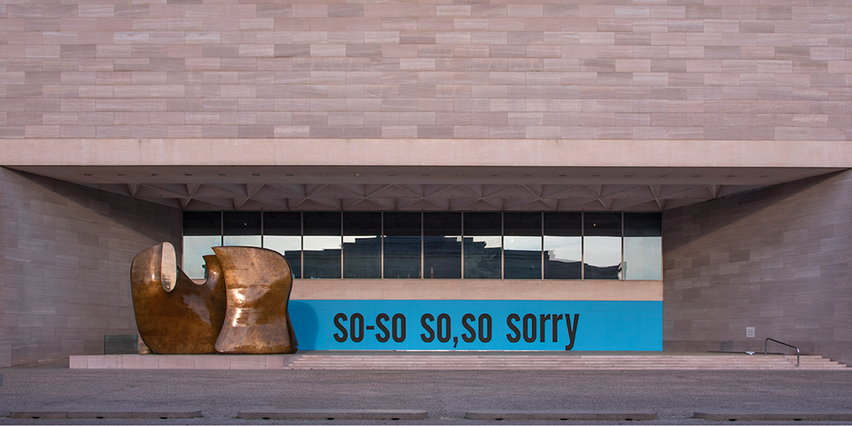 Photograph of the exeterior terrace of the East Building of the National Gallery of Art with a blue painted wall with the words so-so so, so sorry painted in black.