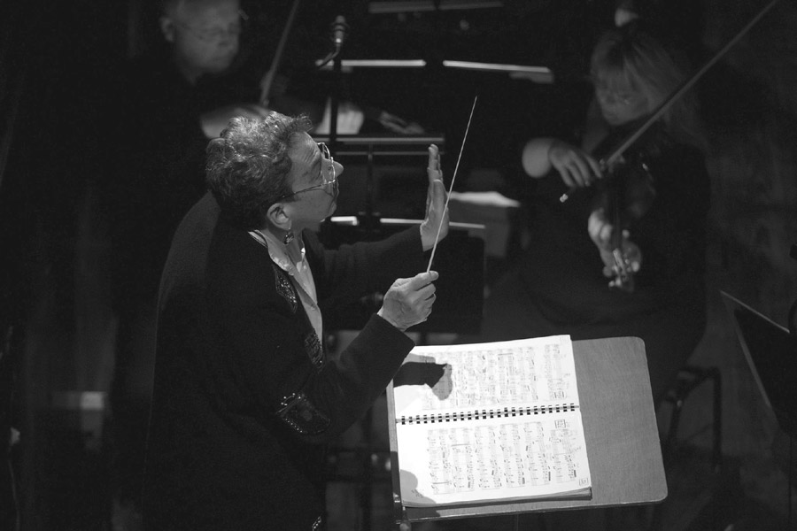 Black and white photograph of Gillian Anderson conducting an orchestra