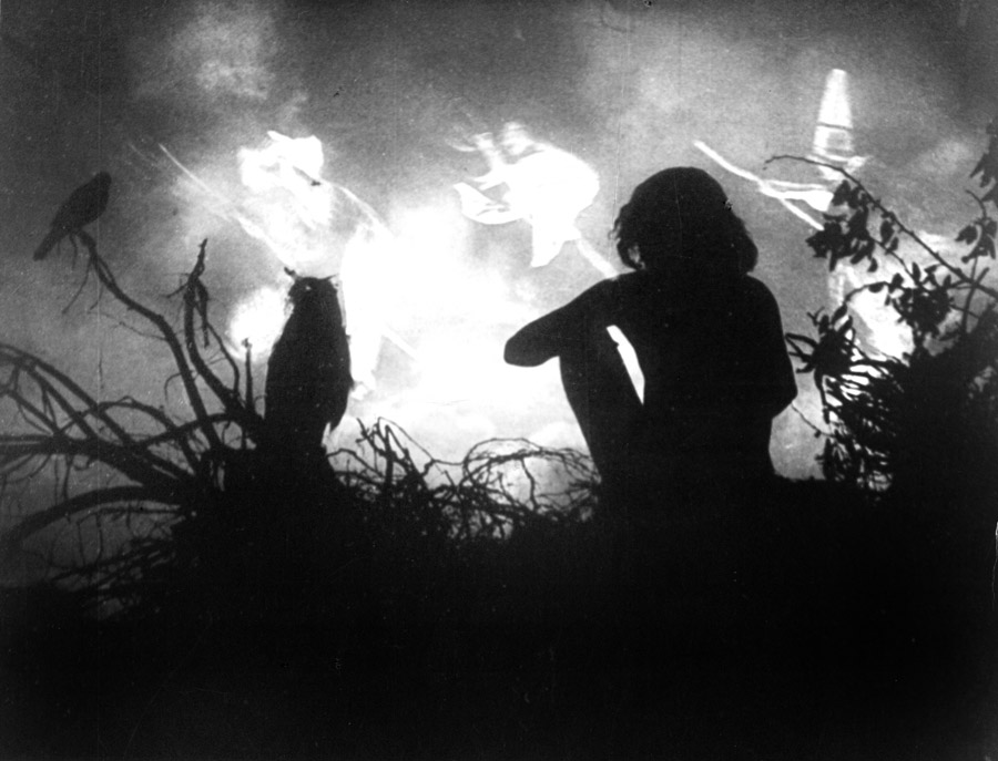 Black and white film still from Häxan (1922) showing a the siloutte of a seated person watching silouttes of three witches on broomsticks circling a fire.