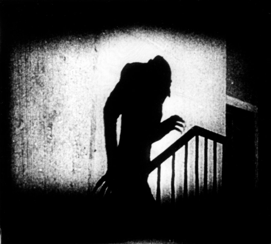 Black and white film still from Nosferatu showing a ghoulish shadowed creature in the shape of a man
