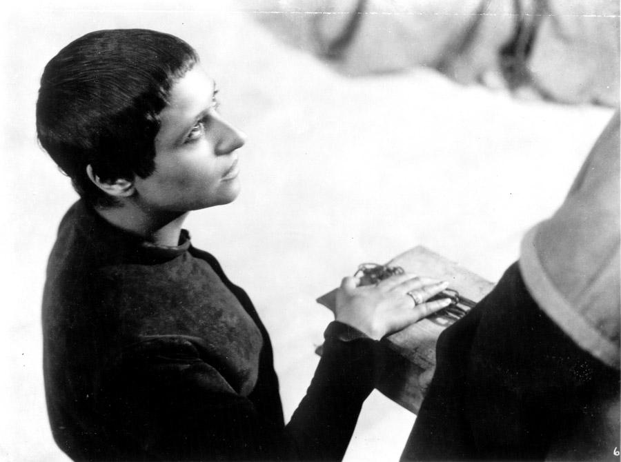 Black and white film still from The Passion of  Joan of Arc depicting a woman with short dark hair placing her hand on a book being held by a person wearing a robe that is partially off screen