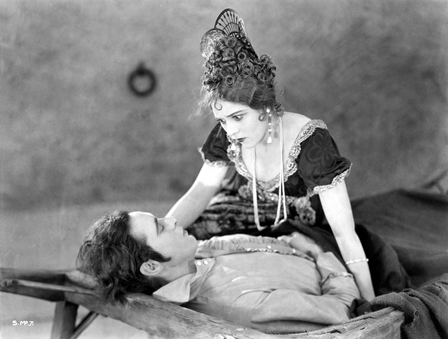 Black and white film still from Rosita (1923) showing a man laying on a cot and a woman looking at the man while seated on the far side of the cot