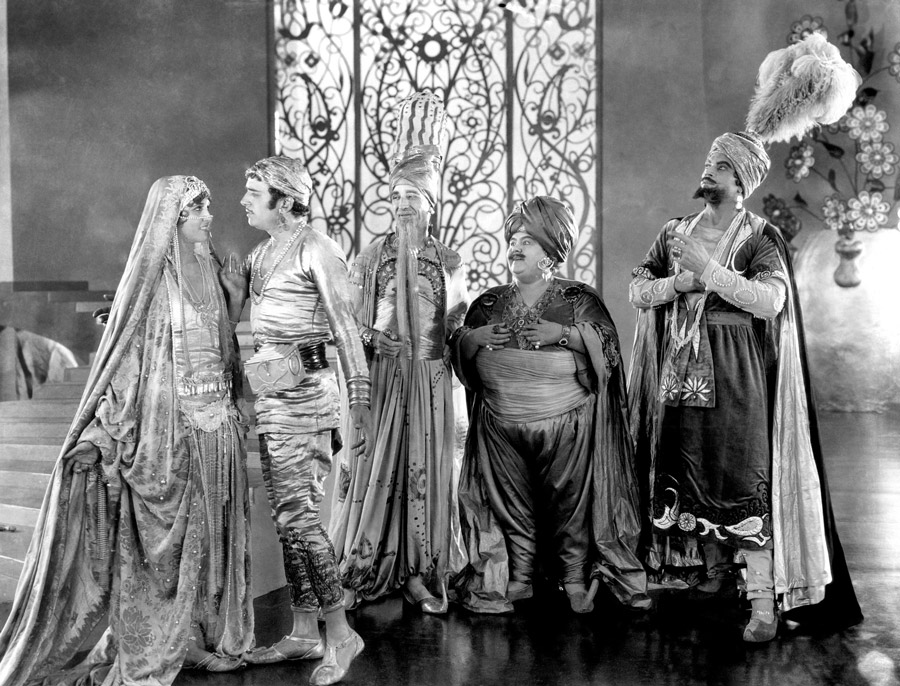 Black and white film still from The Thief of Bagdad showing a man and woman staring into each other's eyes while three men look on in admiration