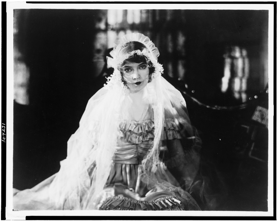 Black and white film still from Way Down East (1920) showing a seated woman wearing a ruffled gown and veil.