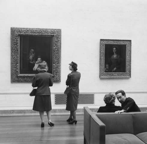 Photo of two women in army uniforms during 1940s looking at paintings in the gallery