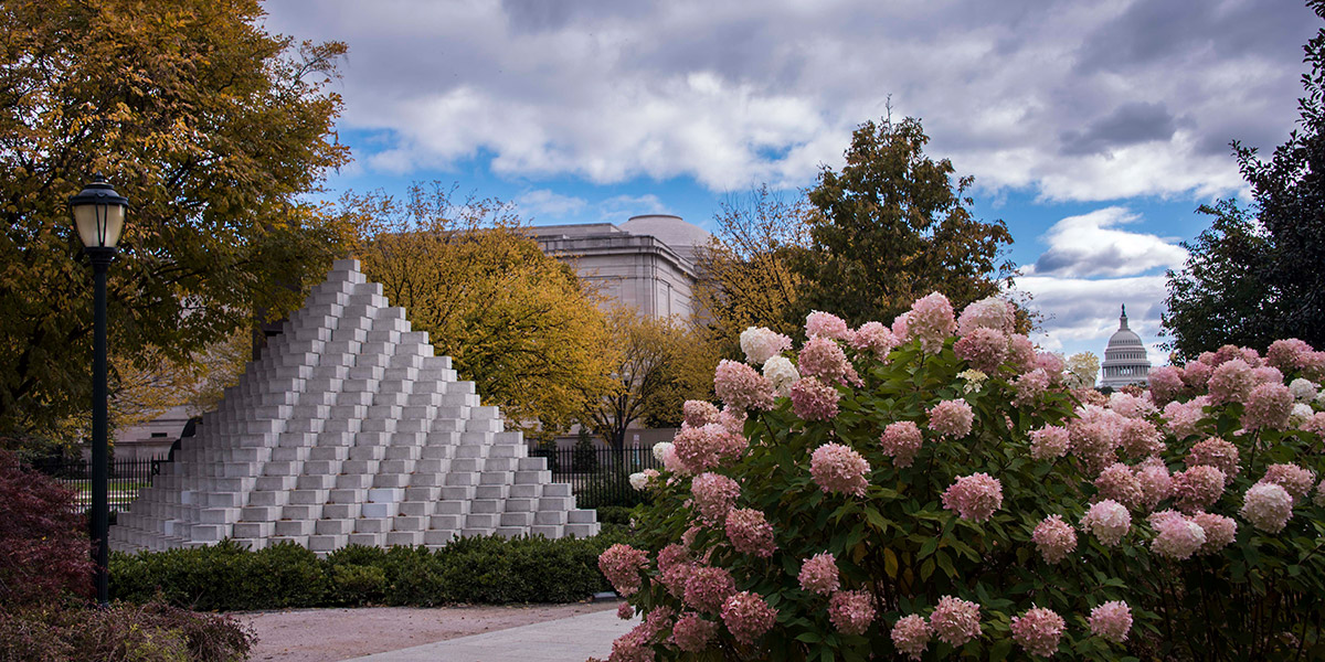 Pyramid-shaped sculpture, pink blooming flowers, and green trees in Sculpture Garden with Capitol in the distance on a sunny day with some white, fluffy clouds in the sky