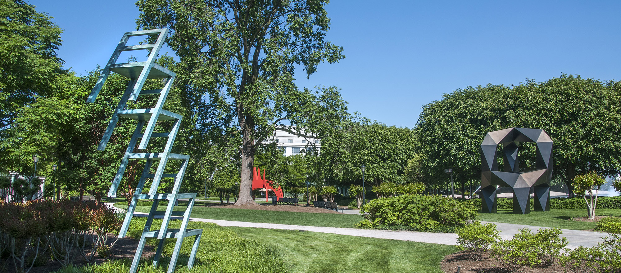 Photo of park with blue sky and green lawn featuring sculpture of five chairs mounted on top of each other