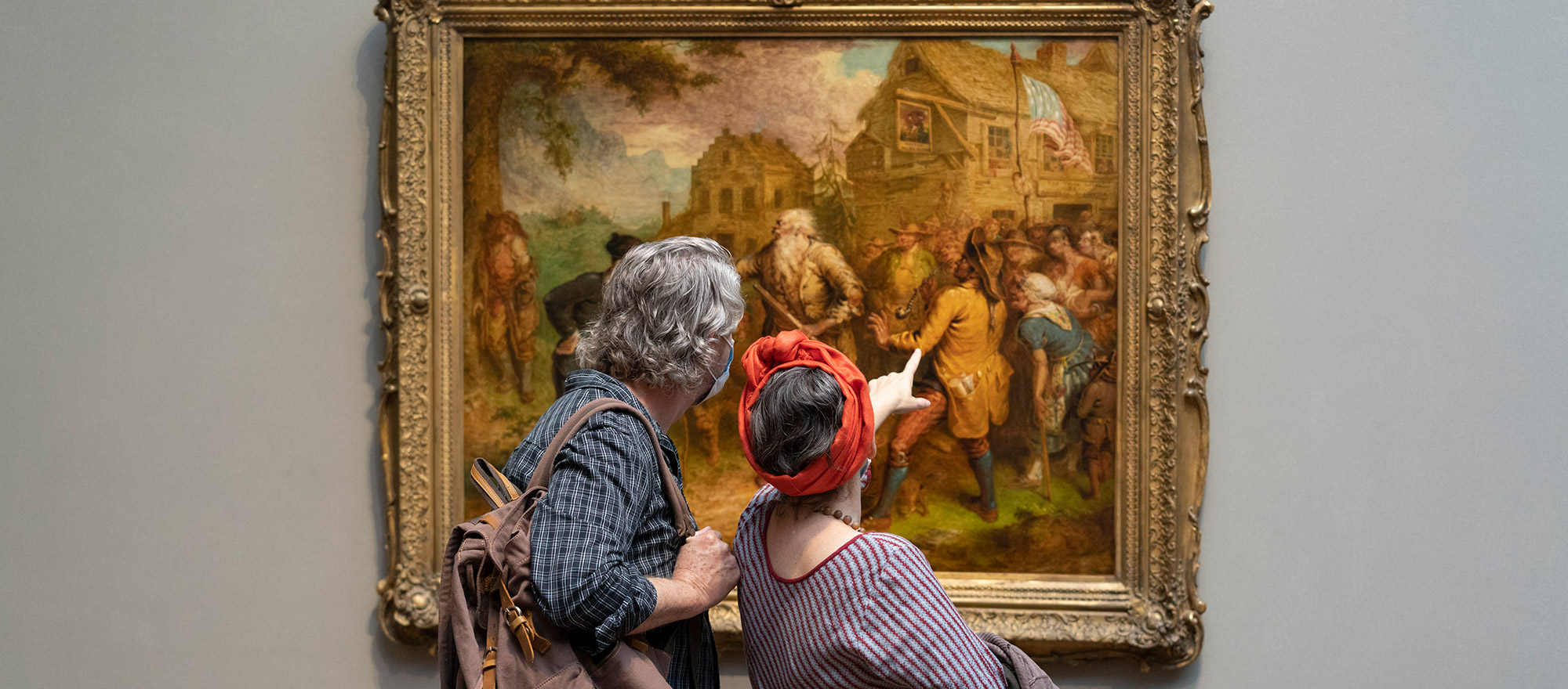 2 museum visitors, a man and a woman, looking at painting. The woman is pointing at the painting.