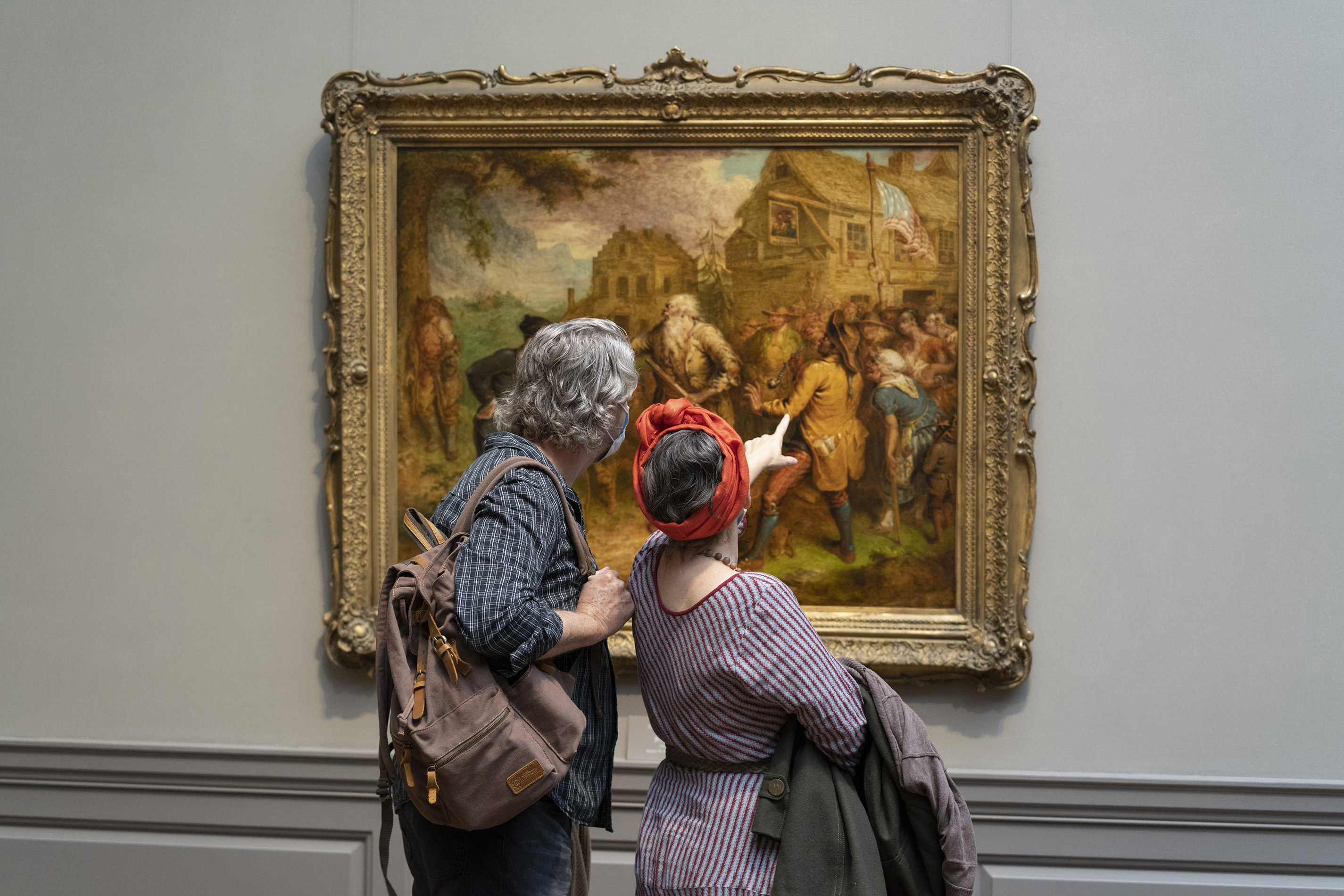 Two people stand together with their backs to the viewer while looking at a painting of a crowd of people. The person on the right gestures with her hand at a detail of the painting.